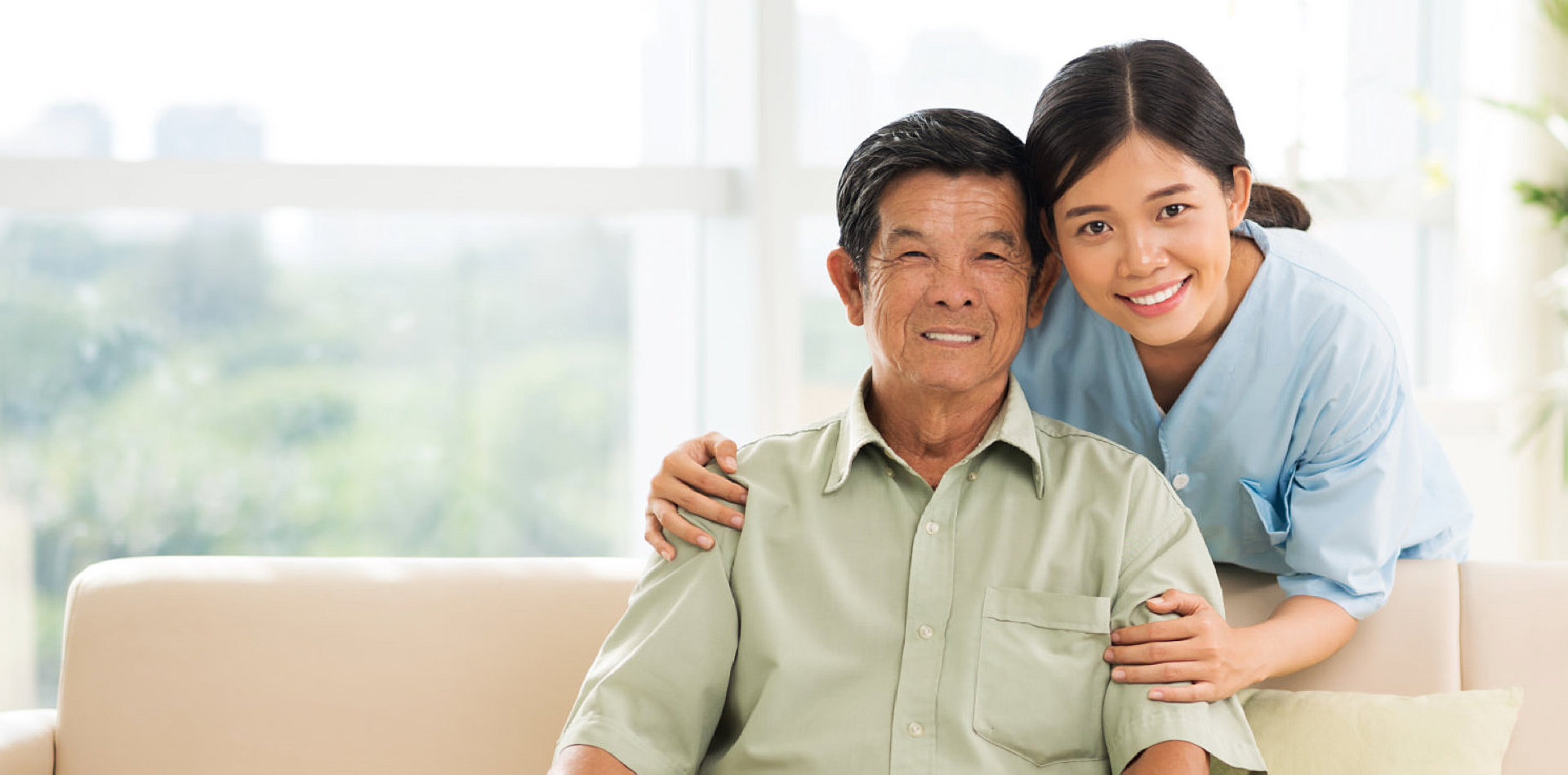 female caregiver and senior man smiling