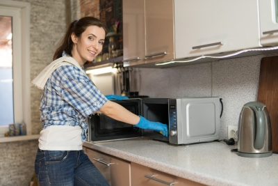 A young woman washes a microwave
