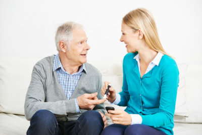 senior man and female caregiver looking at each other