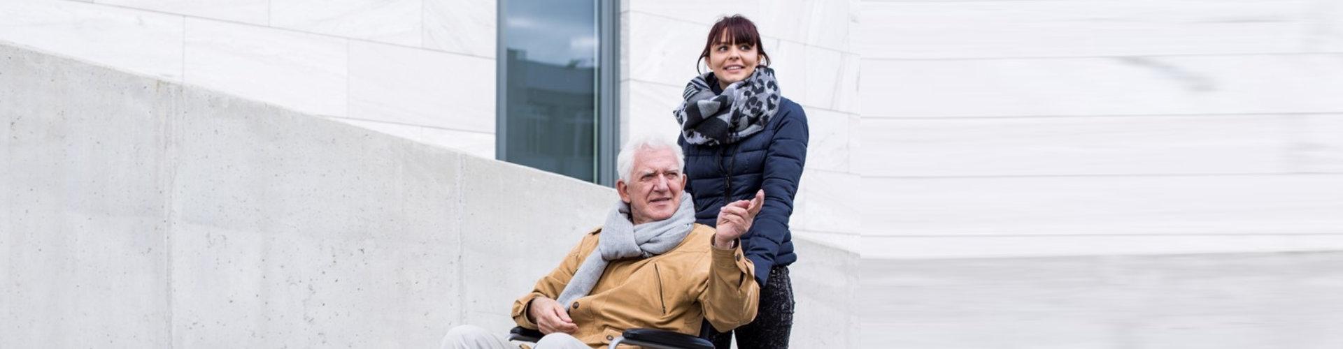 female caregiver and senior man strolling
